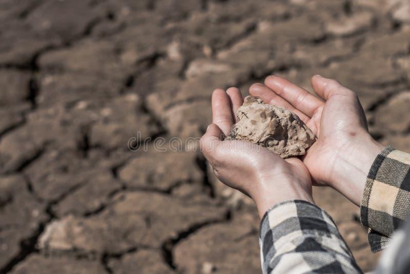 La donna della mano tiene una sporcizia asciutta dell'argilla con disperazione su suolo asciutto fotografia stock