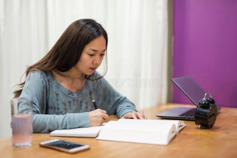 La donna dello studente ha letto il libro e prende nota immagini stock
