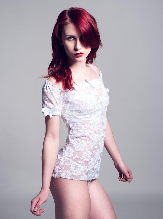 La donna dentro vede attraverso la camicia bianca esaminare la macchina fotografica immagini stock