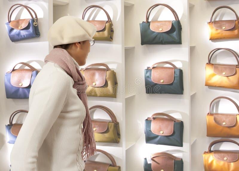 La donna di acquisto sceglie la borsa di signora in stor immagine stock