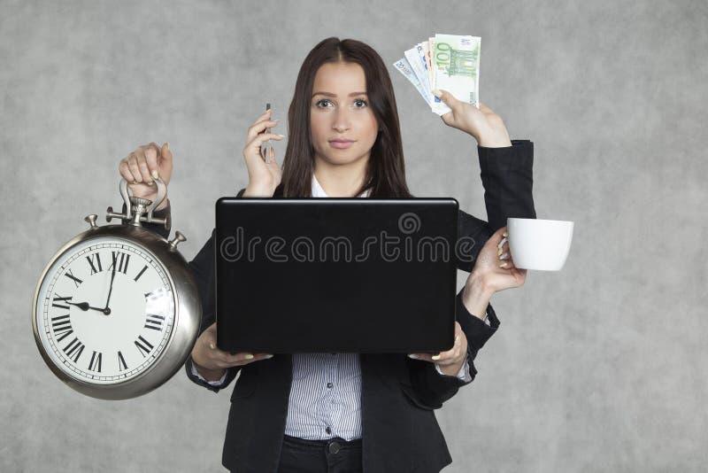 La donna di affari è molto a funzioni multiple fotografie stock
