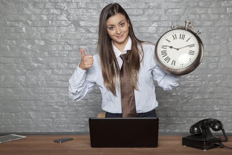 La donna di affari è sempre in tempo, pollici su immagine stock