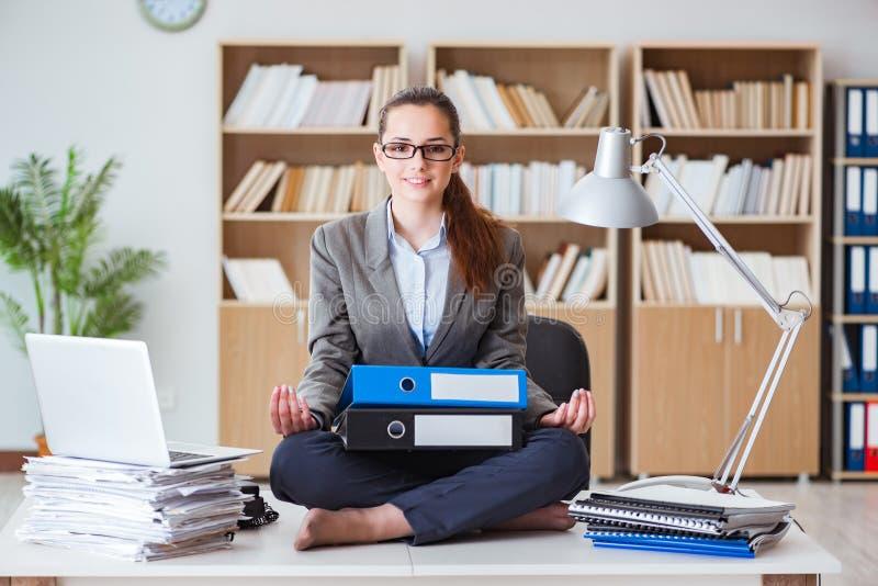 La donna di affari arrabbiata occupata che si siede sullo scrittorio in ufficio fotografie stock libere da diritti