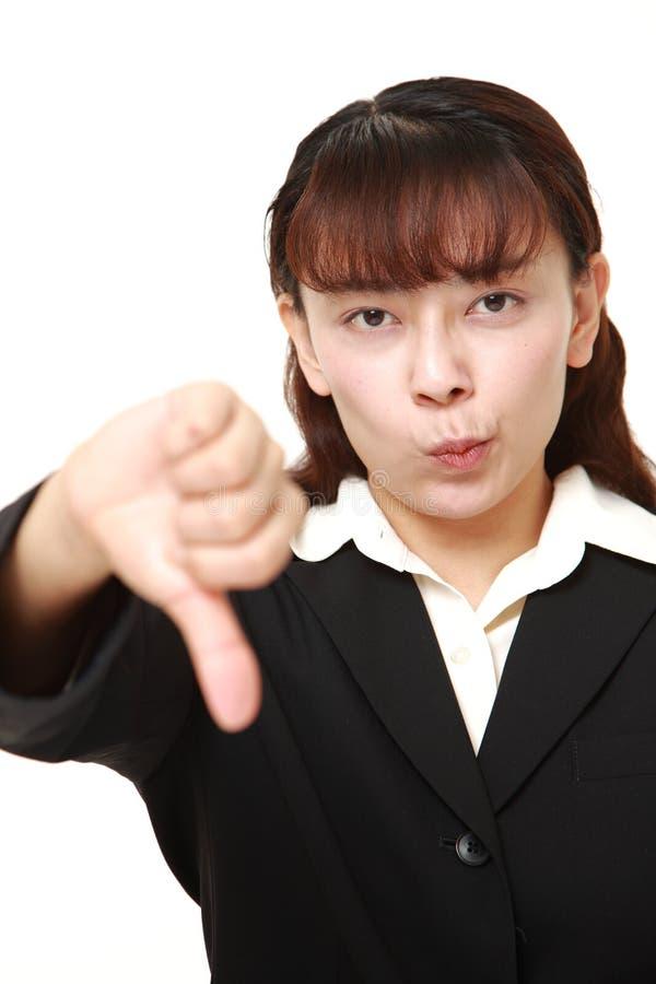 La donna di affari asiatica con i pollici giù gesture immagini stock libere da diritti