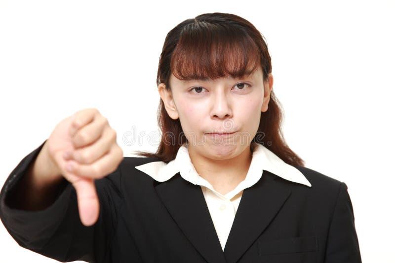 La donna di affari asiatica con i pollici giù gesture fotografia stock libera da diritti