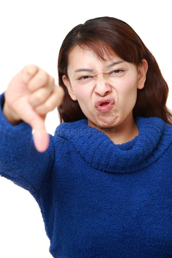 La donna di affari asiatica con i pollici giù gesture fotografie stock