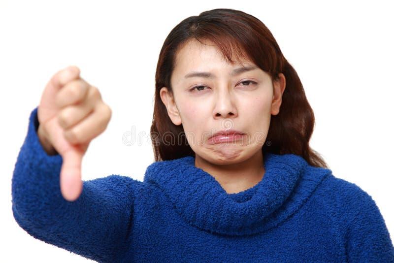 La donna di affari asiatica con i pollici giù gesture fotografie stock libere da diritti