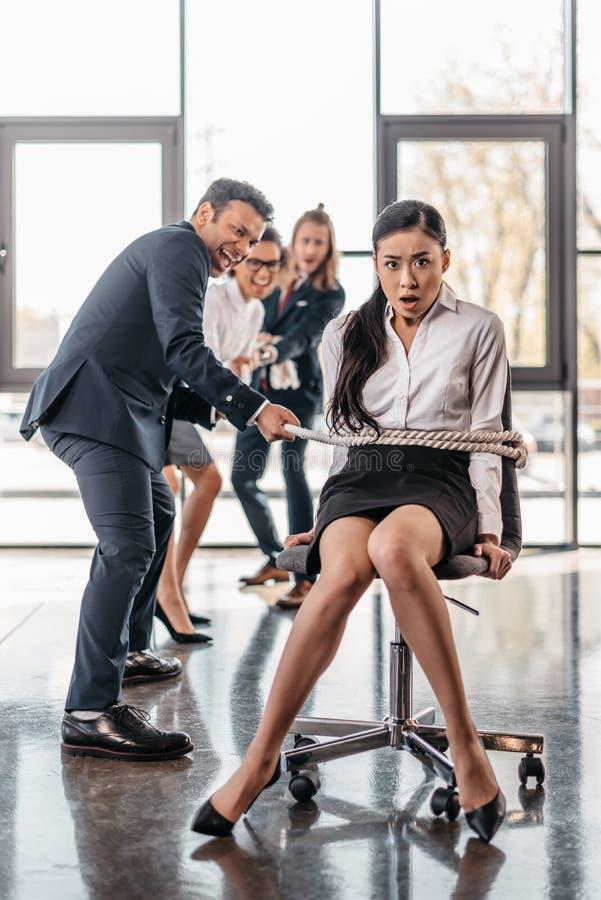 La donna di affari asiatica limita con la corda sulla sedia e sul gruppo multiculturale di affari che la tirano immagine stock