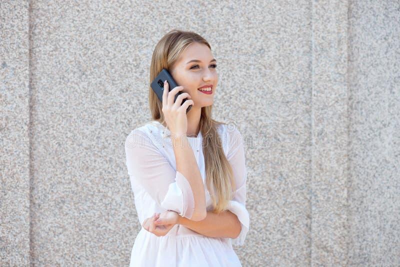 La donna di affari bionda attraente che parla su un telefono cellulare o scrive un messaggio ad un cliente immagini stock
