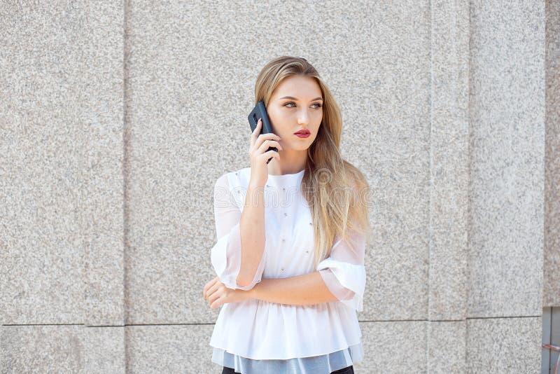 La donna di affari bionda attraente che parla su un telefono cellulare o scrive un messaggio ad un cliente fotografia stock