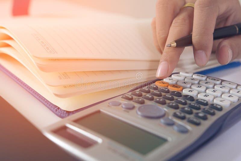 La donna di affari calcola circa costo e facendo l'ufficio di finanza a casa, i responsabili di finanza incaricano, affare di con fotografia stock