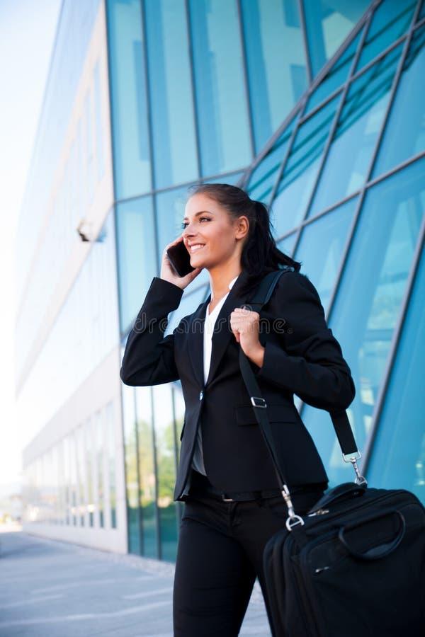 La donna di affari cammina città vicina all'aperto dell'edificio per uffici giù immagine stock