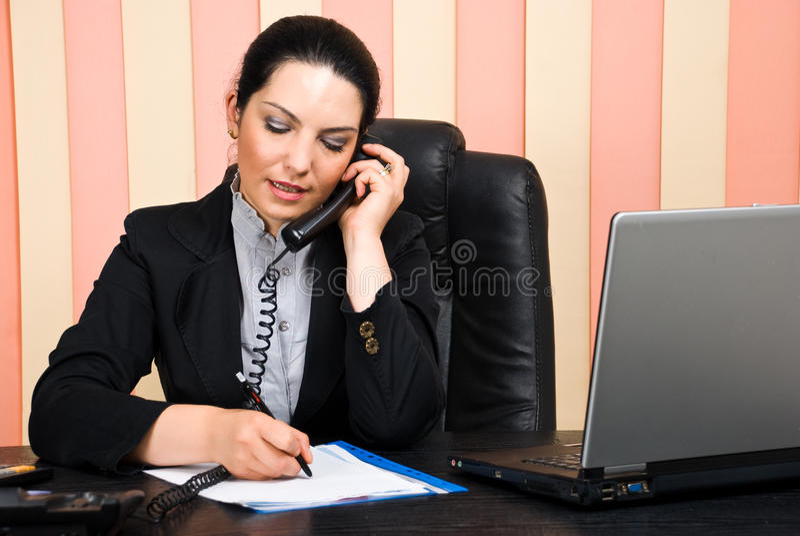 La donna di affari che comunica dal telefono e scrive su documento immagine stock libera da diritti