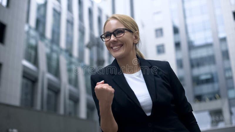 La donna di affari che mostra sì il gesto, si rallegra alla promozione ed alla riuscita carriera fotografia stock libera da diritti