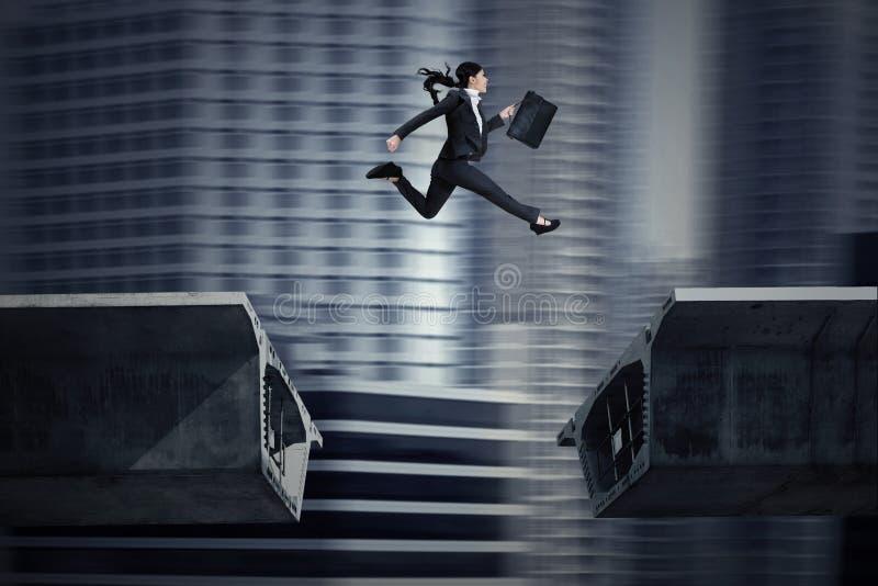 La donna di affari che salta sopra una lacuna nel ponte royalty illustrazione gratis