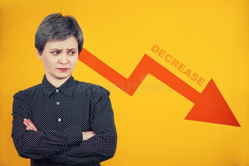 La donna di affari che sembra da parte riflettere stupito come grafico della freccia di reddito sta diminuendo costantemente Conc immagini stock