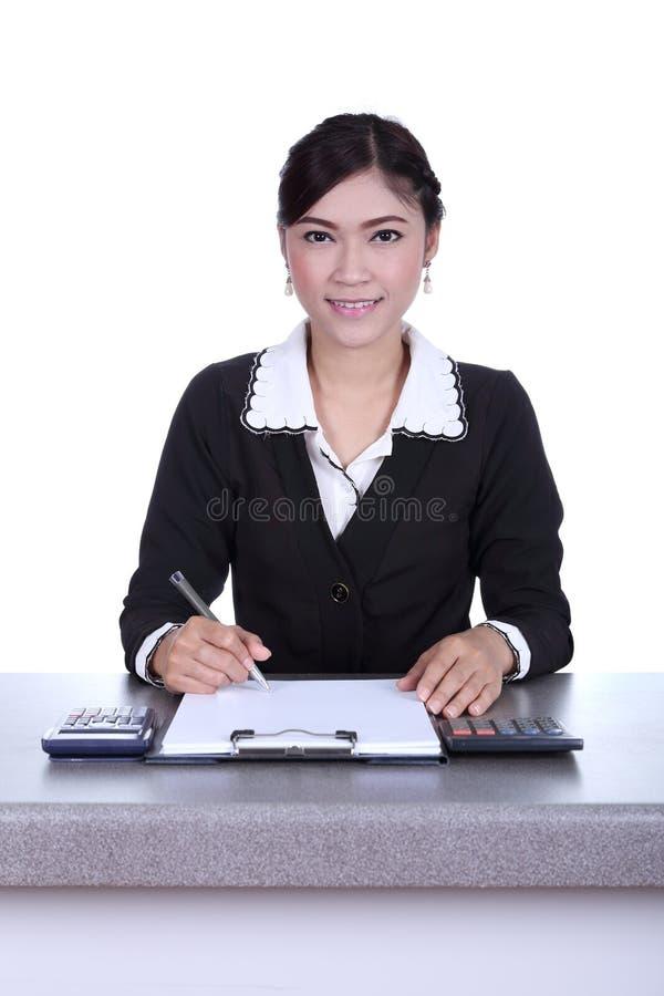 La donna di affari che si siede sul suo scrittorio che tiene una penna che lavora con fa fotografia stock libera da diritti