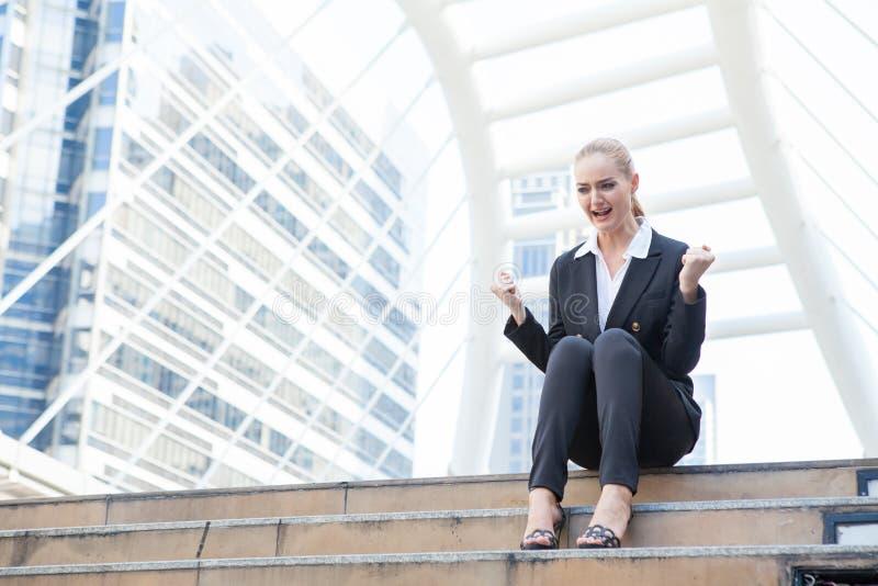 La donna di affari che si siede sulle scale stanche sta gridando e feelin fotografia stock