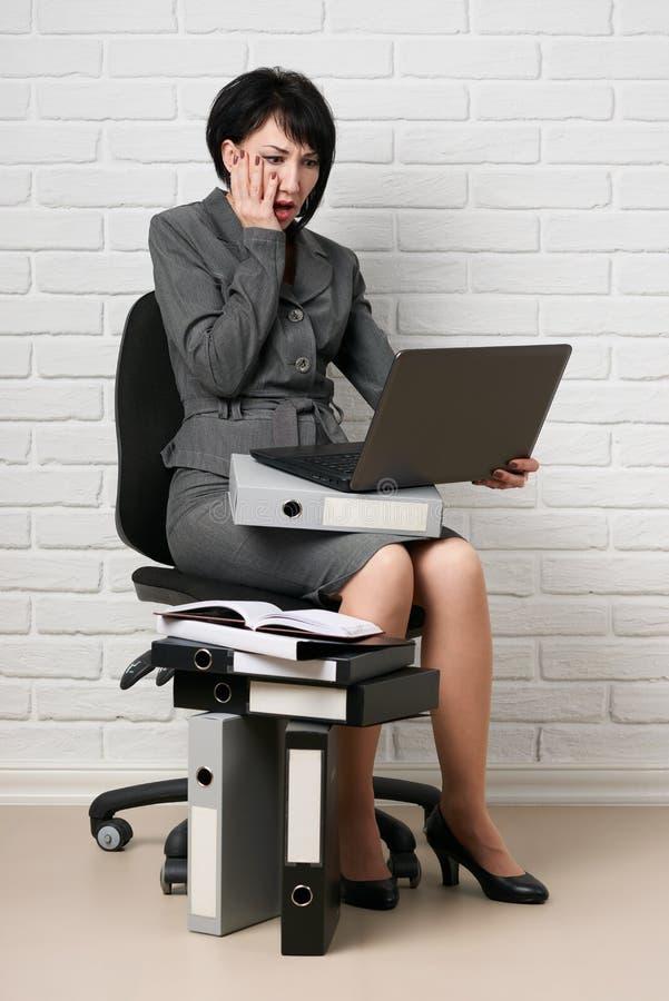 La donna di affari con il computer portatile e le cartelle, vestiti in un vestito grigio posa davanti ad una parete bianca fotografie stock