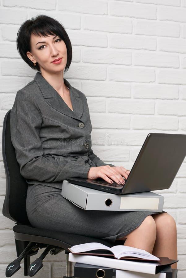 La donna di affari con il computer portatile e le cartelle, vestiti in un vestito grigio posa davanti ad una parete bianca immagine stock libera da diritti
