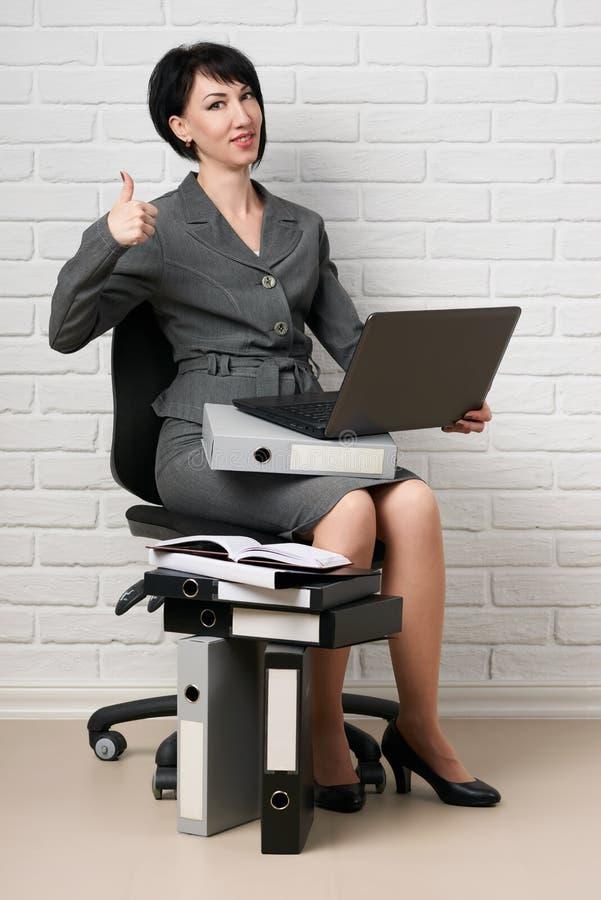 La donna di affari con il computer portatile e le cartelle, vestiti in un vestito grigio posa davanti ad una parete bianca immagini stock libere da diritti