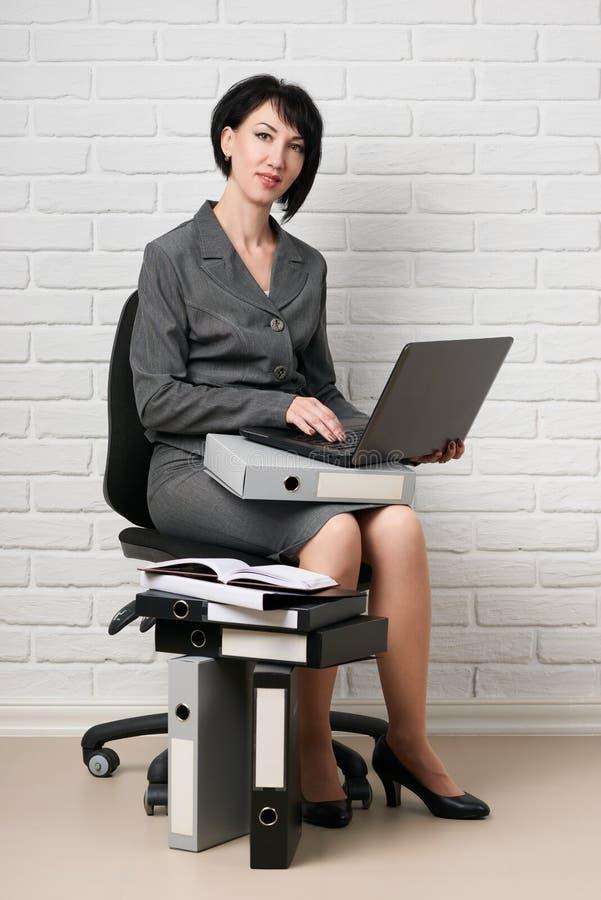 La donna di affari con il computer portatile e le cartelle, vestiti in un vestito grigio posa davanti ad una parete bianca fotografia stock libera da diritti