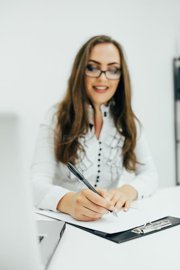La donna di affari con il taccuino nell'ufficio e nella scrittura data sul taccuino fotografie stock