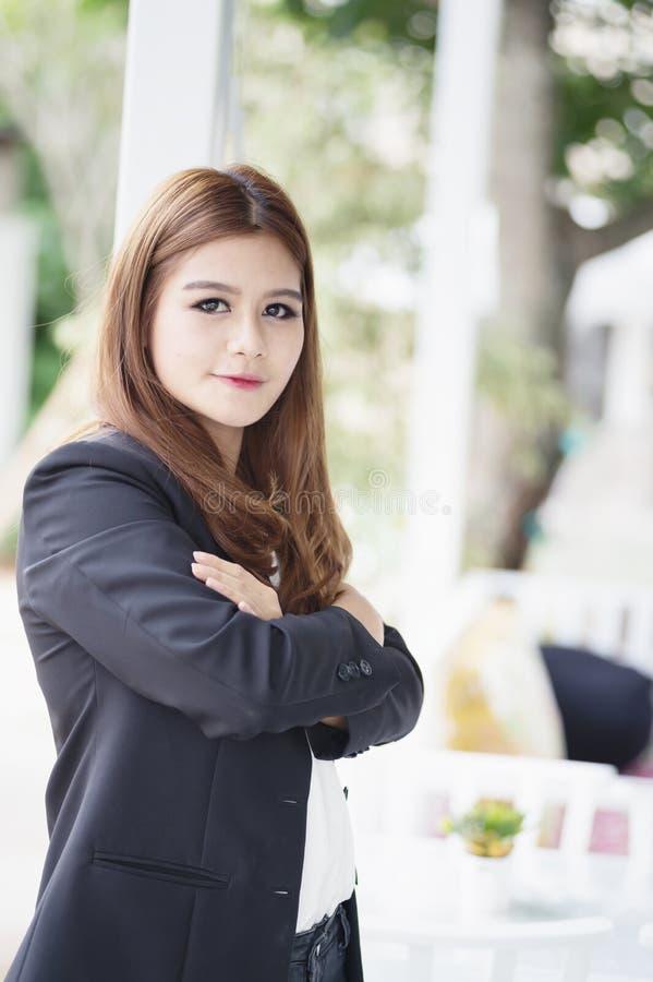 La donna di affari dell'Asia con le armi ha attraversato la condizione nel suo ufficio immagini stock libere da diritti