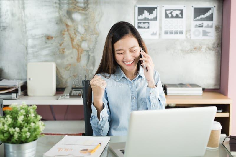 La donna di affari della nuova generazione che per mezzo dello smartphone, donna asiatica sta lavorando felicemente nell'ufficio, immagine stock
