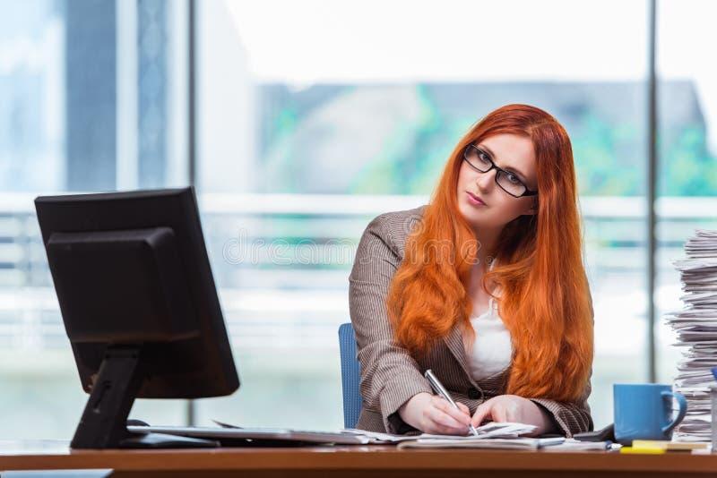 La donna di affari della testarossa che si siede al suo scrittorio nell'ufficio fotografia stock libera da diritti