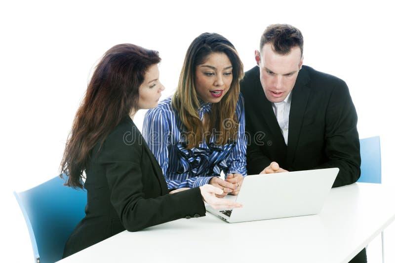 La donna di affari e delle coppie esamina il computer portatile che si siede alla tavola fotografia stock