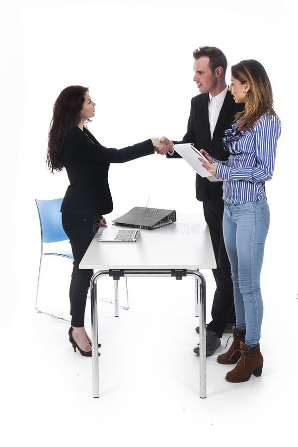 La donna di affari e delle coppie stringe le mani mentre sta alla tavola fotografia stock libera da diritti