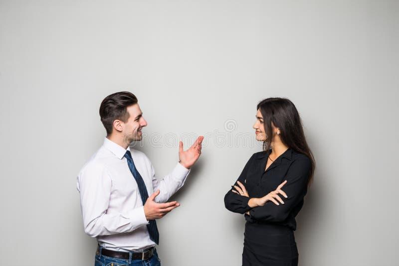 La donna di affari e l'uomo d'affari sorridenti stanno conversando contro fondo grigio fotografia stock