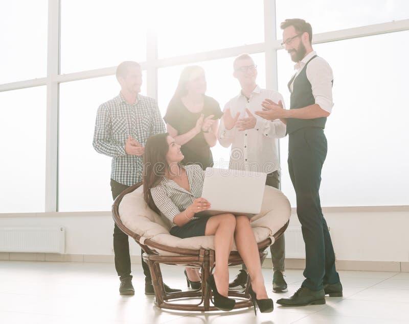 La donna di affari ed il suo gruppo di affari sono nel luogo di lavoro nell'ufficio fotografie stock