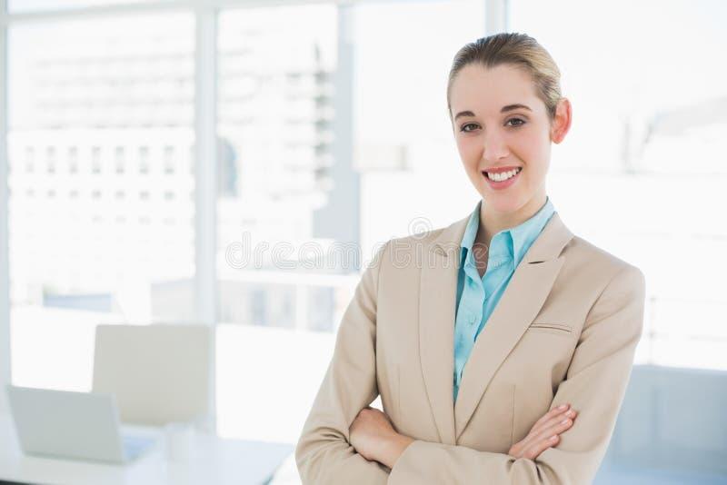 La donna di affari elegante sorridente adorabile che posa con le armi ha attraversato sorridere alla macchina fotografica fotografia stock