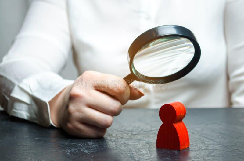 La donna di affari esamina una figura dell'uomo rosso tramite una lente d'ingrandimento Analisi delle qualità personali dell'impi fotografia stock libera da diritti