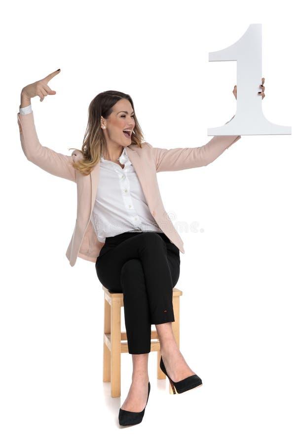 La donna di affari felice tiene uno e guarda per parteggiare mentre celebra immagini stock