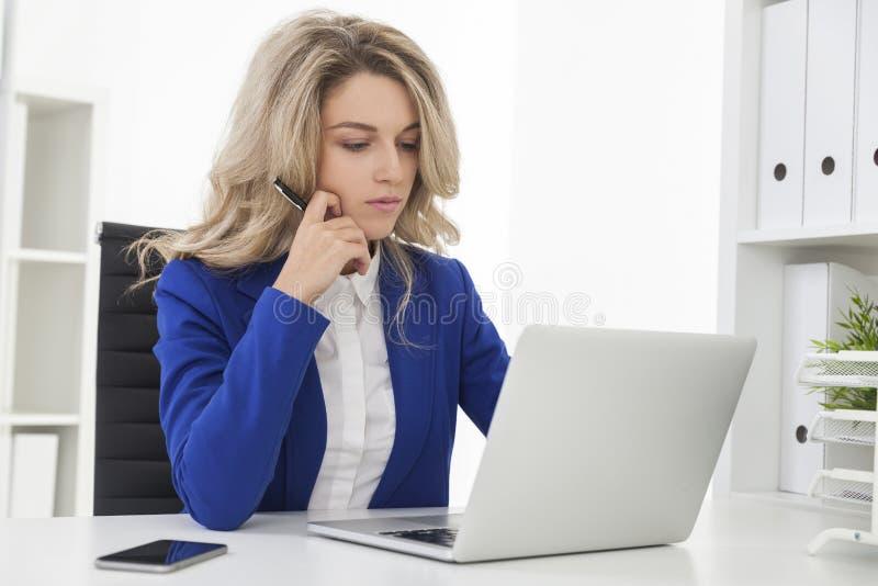 La donna di affari in giacca sportiva blu sta leggendo immagini stock
