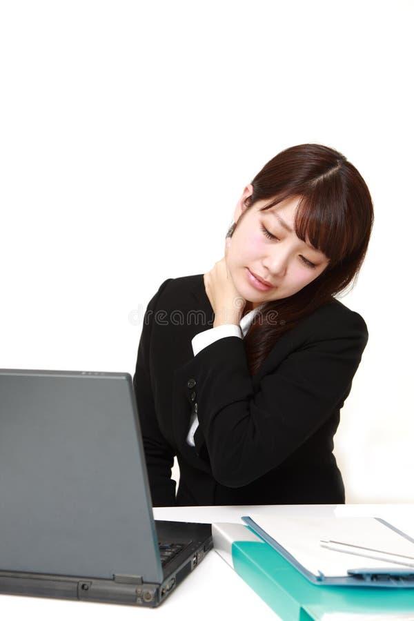 La donna di affari giapponese soffre dal dolore del collo immagine stock libera da diritti