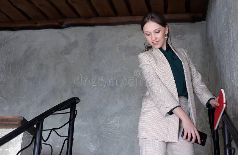 La donna di affari graziosa sta parlando su un telefono sulle scale immagini stock