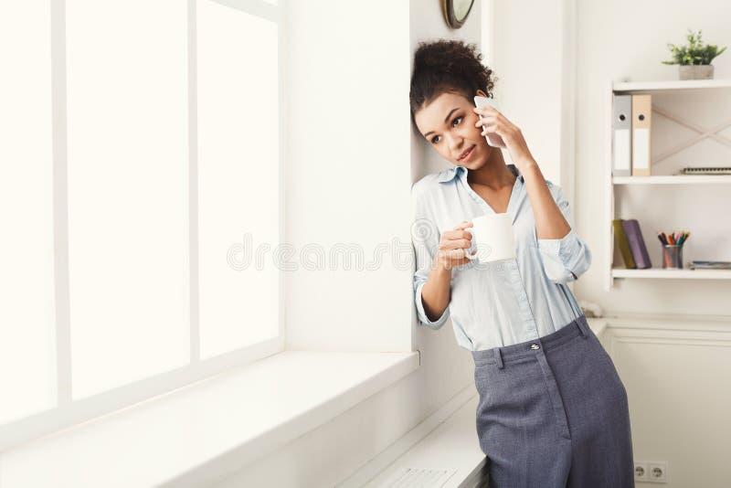 La donna di affari ha conversazione del telefono vicino alla finestra dell'ufficio fotografie stock libere da diritti