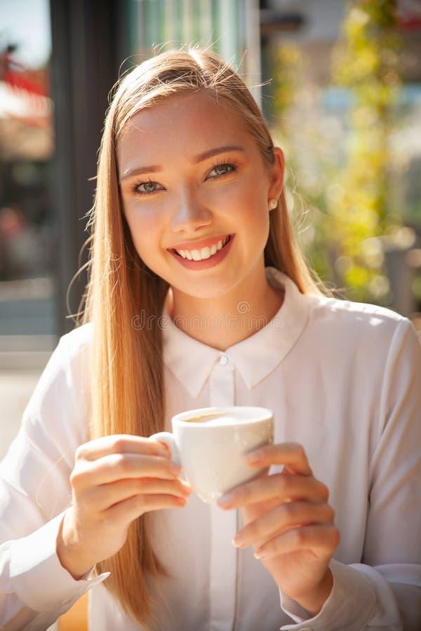 La donna di affari ha una pausa caffè e beve il caffè in una barra fotografie stock