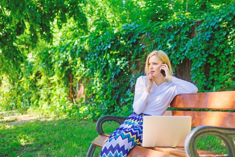 La donna di affari lavora il parco con lo smartphone del computer portatile La chiamata dello smartphone della ragazza risolve il fotografia stock