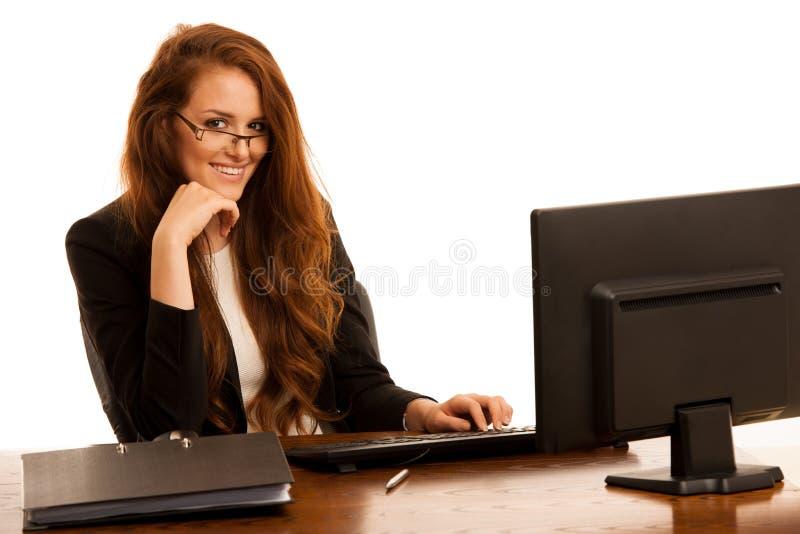 La donna di affari lavora nell'ufficio che controlla la base di dati sul computer fotografia stock