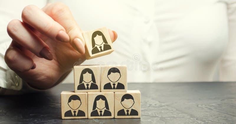 La donna di affari mette un cubo di legno con l'immagine dei lavoratori Concetto misto del personale Direzione del personale in u immagine stock