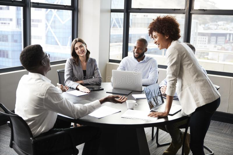 La donna di affari nera millenaria sta ascoltante i colleghi corporativi ad una riunione, fine su immagine stock libera da diritti