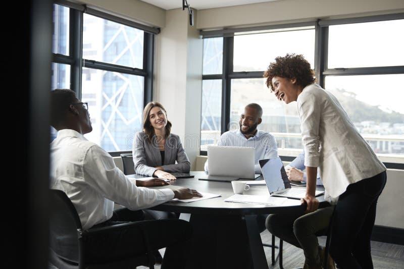 La donna di affari nera millenaria sta ascoltante i colleghi corporativi ad una riunione, fine su fotografia stock libera da diritti