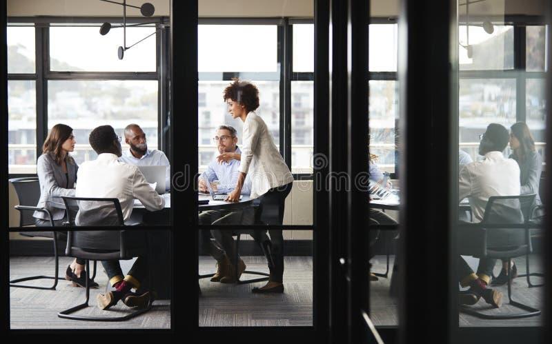 La donna di affari nera millenaria sta parlante ai colleghi ad una riunione, vista attraverso la parete di vetro immagine stock