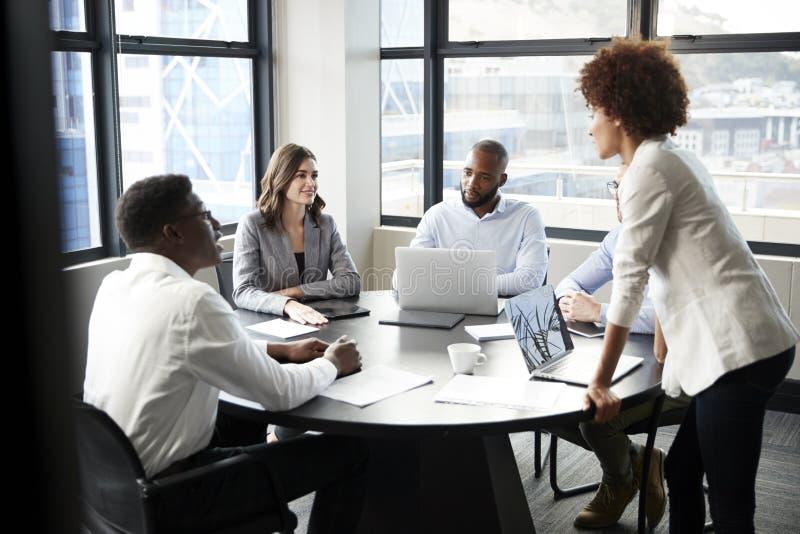La donna di affari nera millenaria sta parlante ai colleghi corporativi ad una riunione, fine su immagine stock libera da diritti