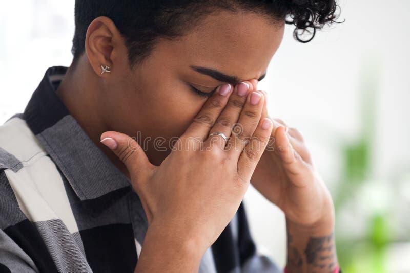 La donna di affari nera turbata ritiene la seduta indisposta nell'ufficio immagine stock